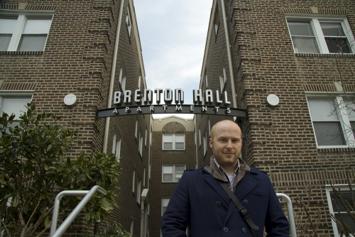 Josh Korwin in front of Brenton Hall Apartments sign, Narberth, Pennsylvania