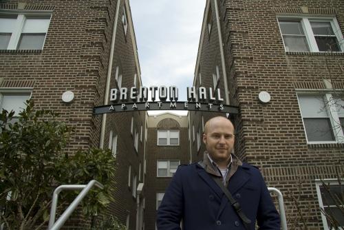 Josh Korwin in front of Brenton Hall Apartments sign, Narberth, Pennsylvania