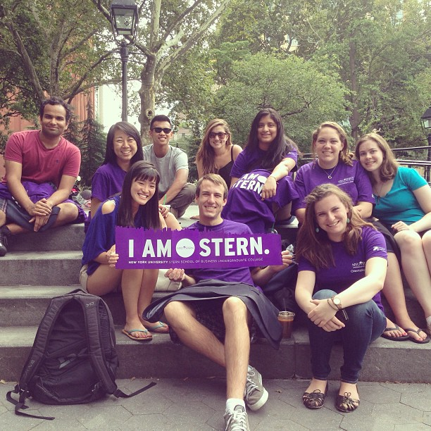 NYU Stern students posing with banner